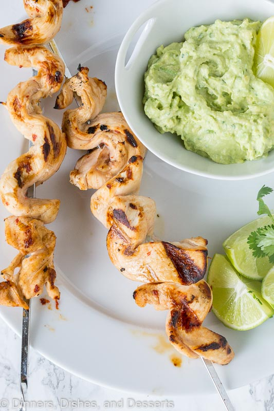 grilled chicken on skewers with avocado dipping sauce on a plate