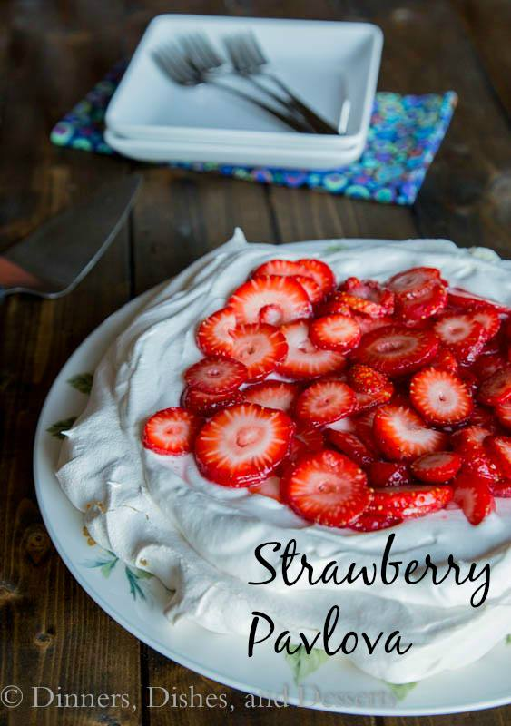 pavlova topped with whipped cream and sliced strawberries