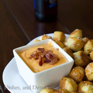 beer cheese dip in a bowl with pretzel bites