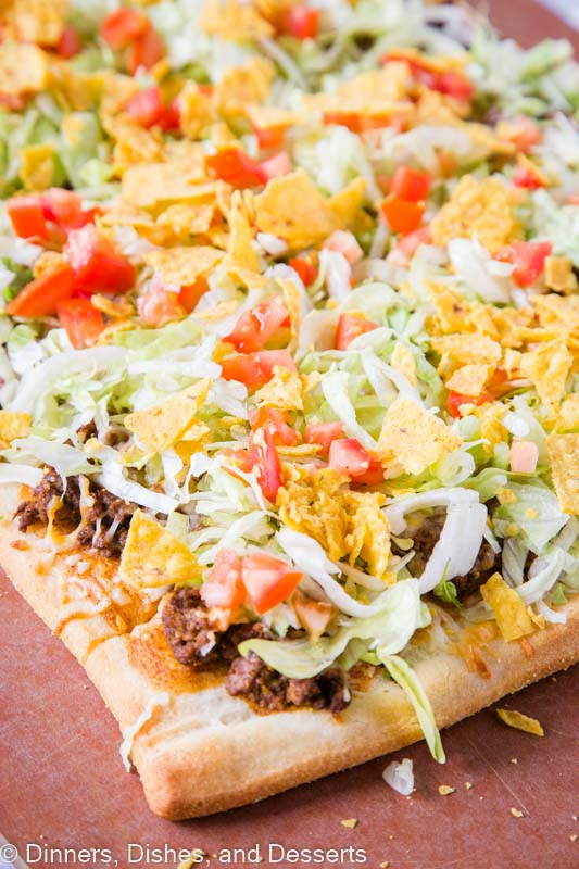 Taco pizza with refried beans, taco sauce, taco meat, cheese, lettuce, tomatoes and tortilla chips!