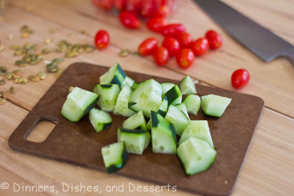 diced cucumbers on cutting board with tomatoes in the background