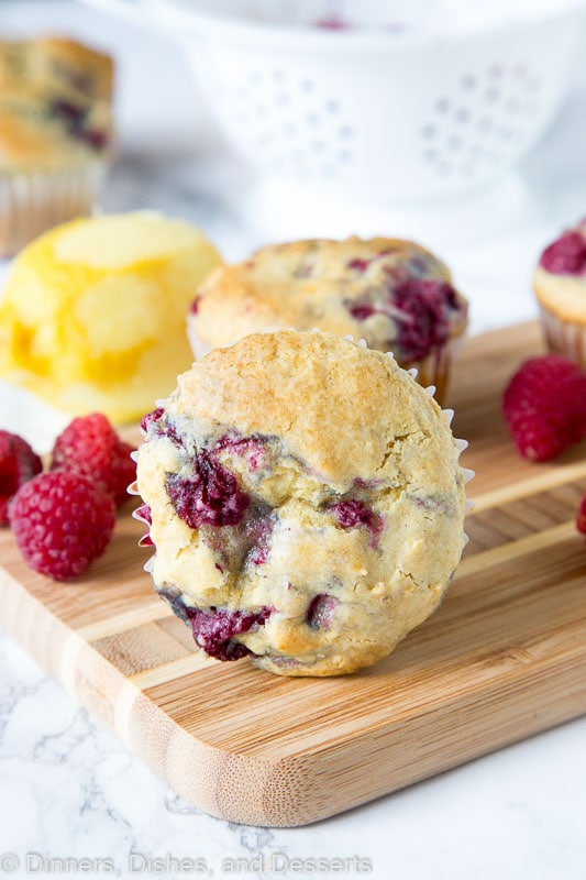 a raspberry muffin on a wooden board with raspberries and lemon next to it