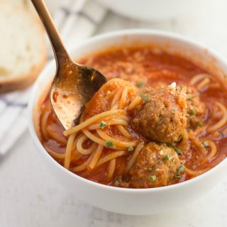 spaghetti and meatball soup in a bowl with a spoon