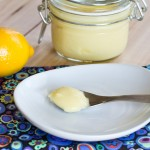 lemon curd on spoon on white plate with lemons on background