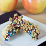 Chocolate-Granola Apple Wedges on white plate with apples in the background