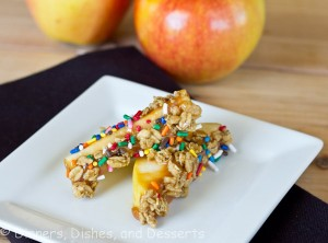 caramel-Granola Apple Wedges on white plate with apples in the background
