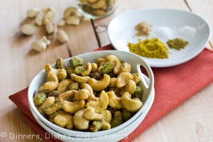 Indian Spiced Nuts in white bowl with plate of spices in background