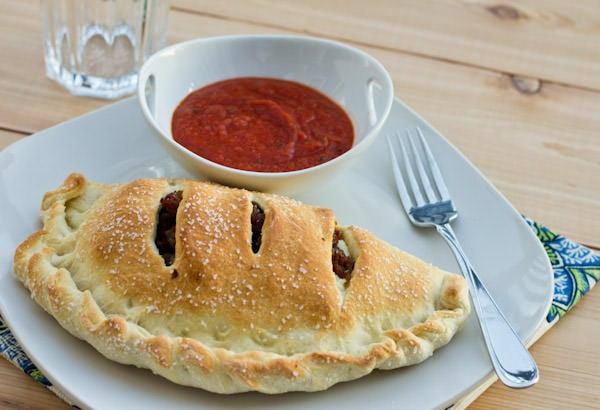 calzone on a plate with red sauce