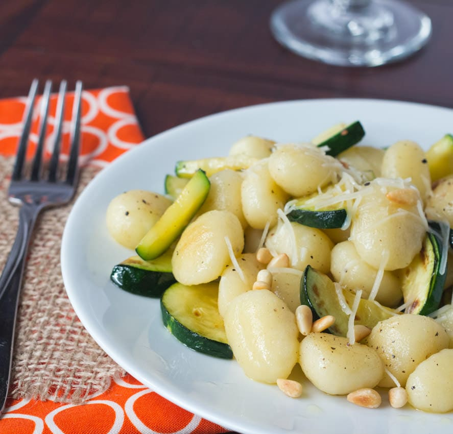 brown butter gnocchi with veggies and pinenuts on a plate