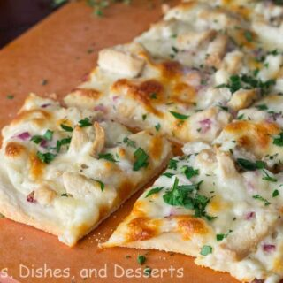 roasted garlic chicken and herb white pizza on a board