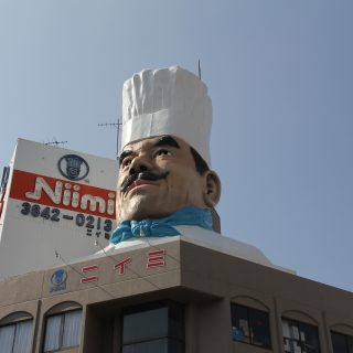 A large tower that has a chef on the side of a building
