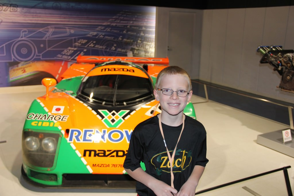 A kid standing in front of a car