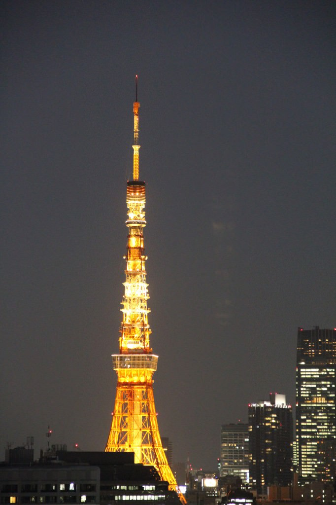 A large clock tower towering over Tokyo Tower at night