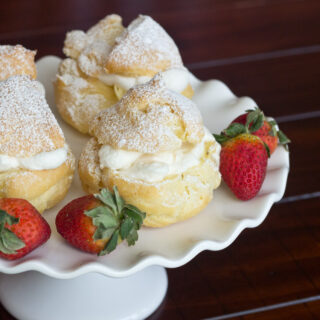 A plate of food cream puffs on a table, with Cream