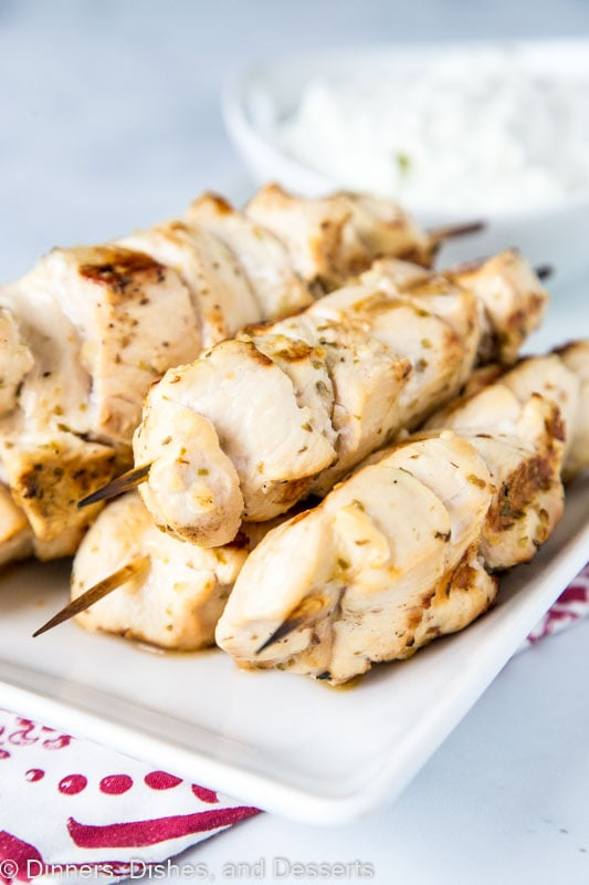 Chicken Souvlaki skewers on a white plate with homemade tzatziki sauce
