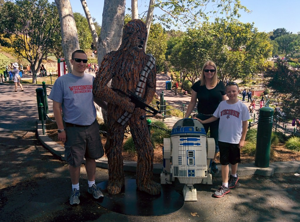 people standing by chewbacca and r2d2 lego figures