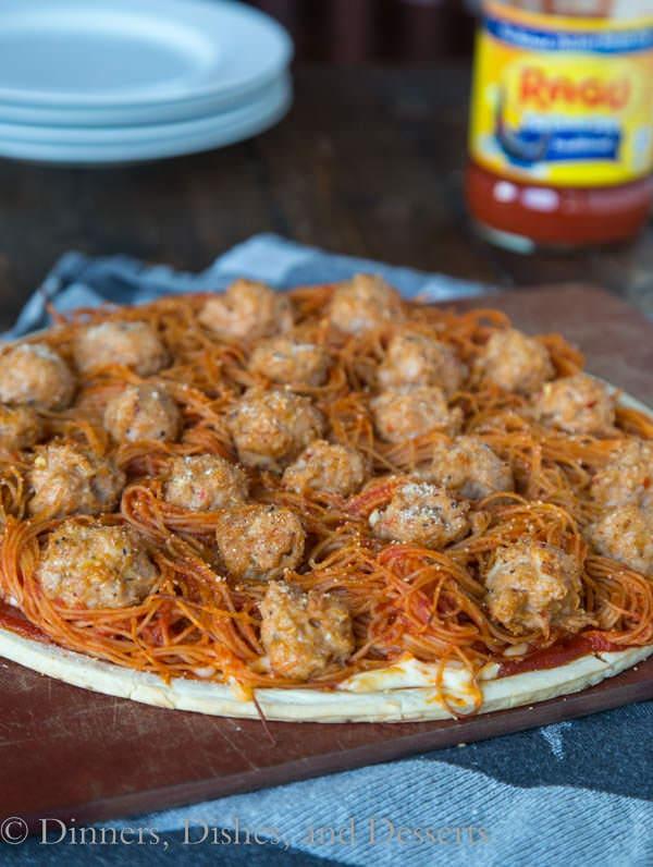 spaghetti and meatball pizza on a board