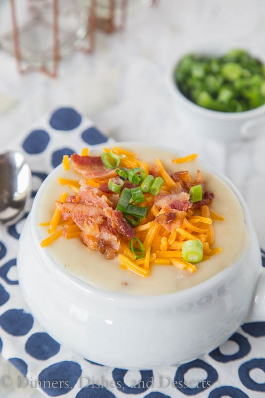 potato soup in a bowl with bacon, cheese, and onions