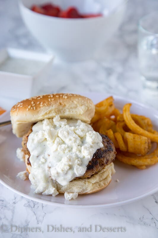 Greek Turkey Burgers - a great way to have burger night with a delicious twist! Greek flavored turkey burgers topped with tzatziki sauce and feta cheese!