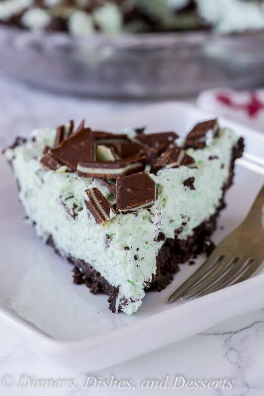 No Bake Mint Chocolate Chip Pie - a creamy mint pie with chocolate chips, topped with Andes mints, all in an Oreo crust! Such an easy no bake recipe for those hot days.