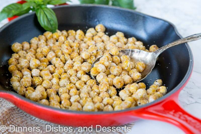 chickpeas in a skillet with a spoon