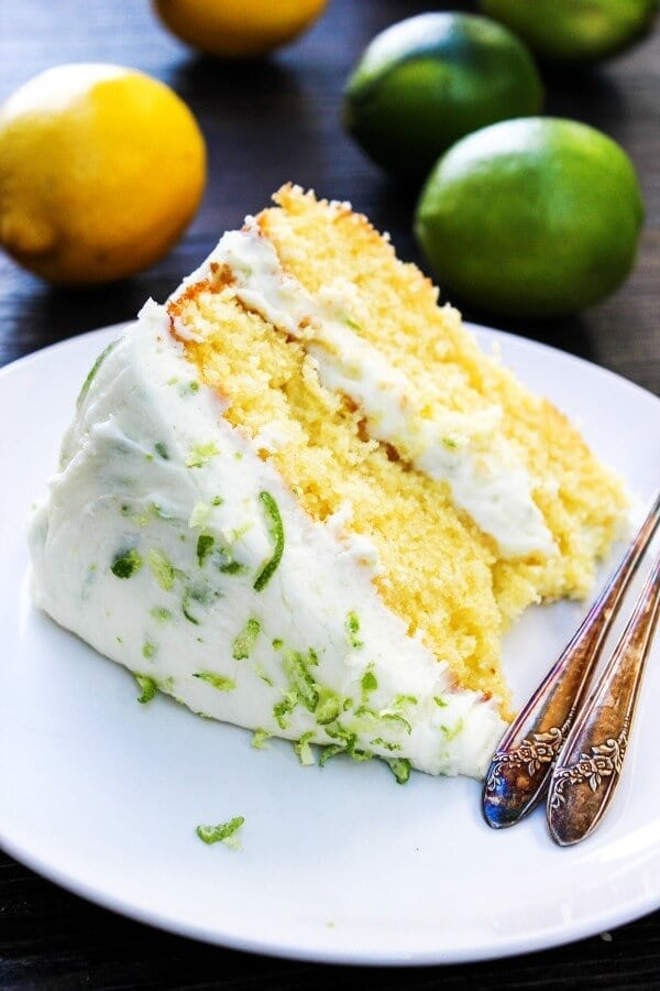 Lemon Lime Layer Cake on a white plate with lemons and limes.