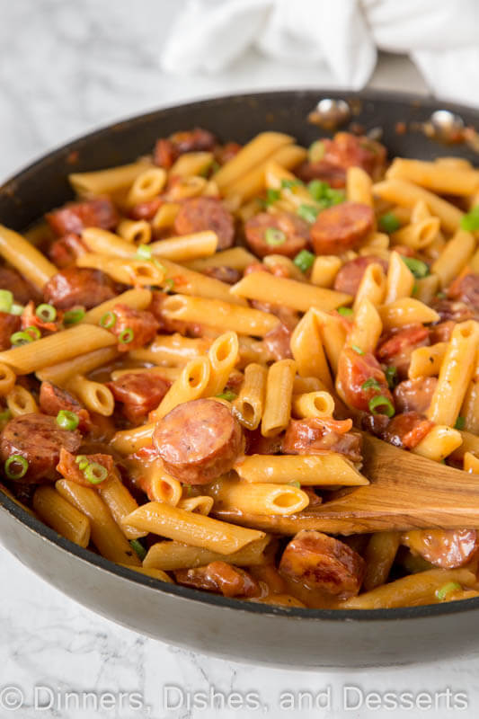 A dish is filled with food, with pasta and Sausage