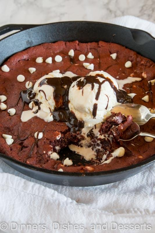 Red velvet skillet cookie in a skillet with a spoon