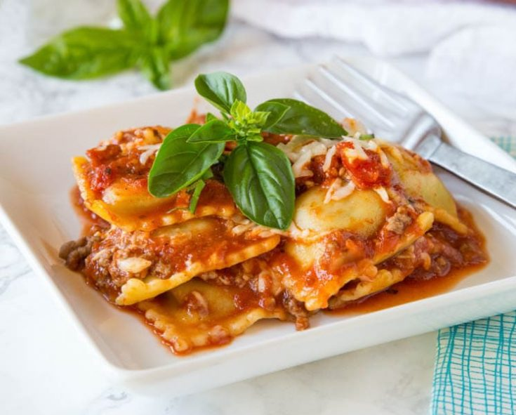 baked ravioli with basil on a plate