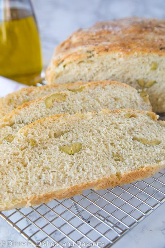 A piece of bread on a plate, with Olive and No-knead bread