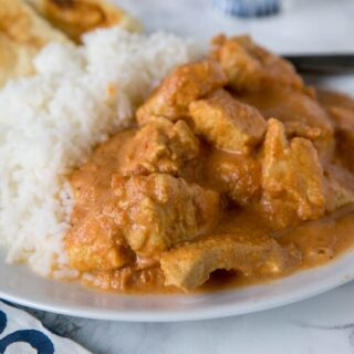 A close up of a plate of food with indian butter chicken and rice
