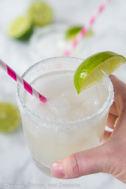 hand holding margarita in a glass with lime wedge and pink straw