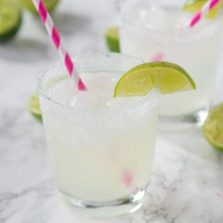 margarita in a glass with lime wedge and pink straw