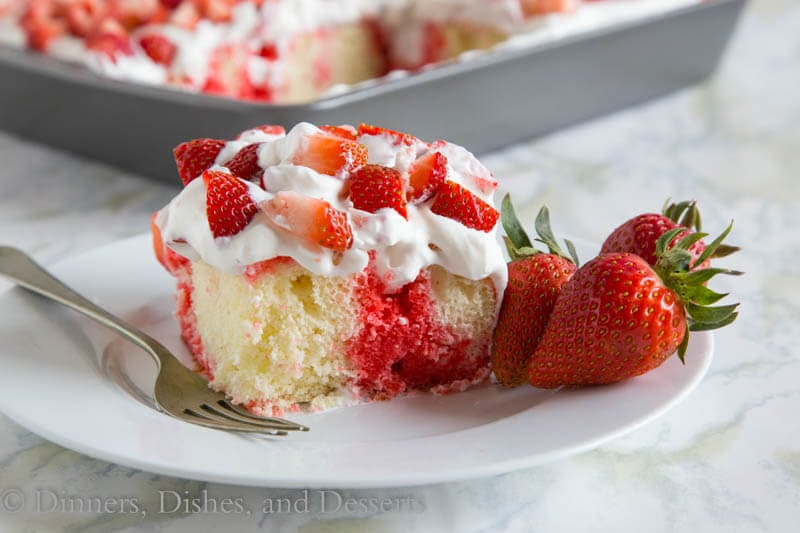 Poke cake with strawberry jello filling the holes and homemade whipped cream on top