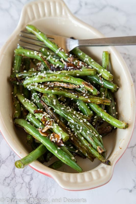 roasted green beans in a dis with sesame seeds and a fork