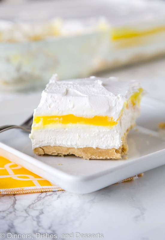 A piece of cake on a plate, with Lemon and Cream layers