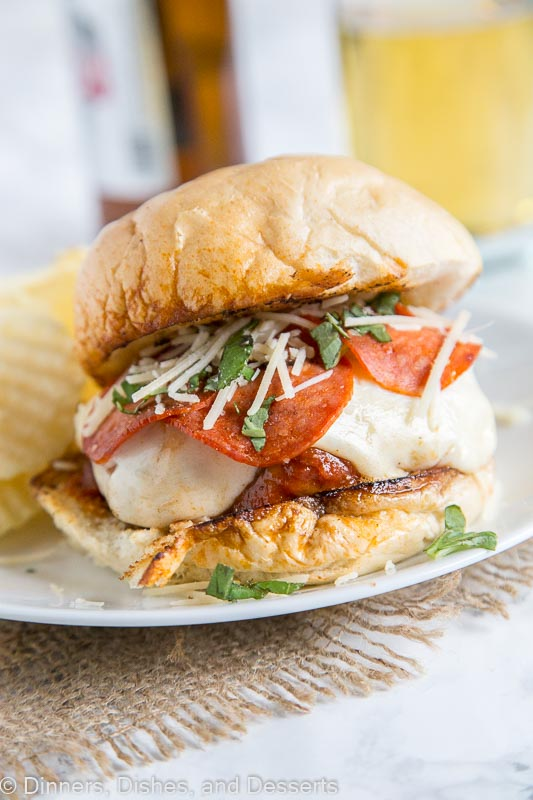 A close up of pepperoni pizza burger on a plate with potato chips