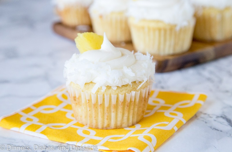 pineapple cupcakes with coconut and pineapple piece on a table
