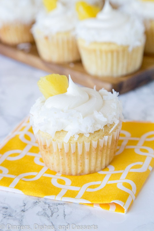 A close up of A close up pineapple cupcakes with coconut and pineapple piece