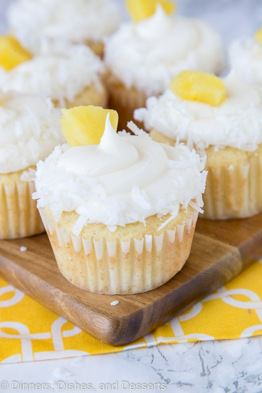 A close up pineapple cupcakes with coconut and pineapple piece