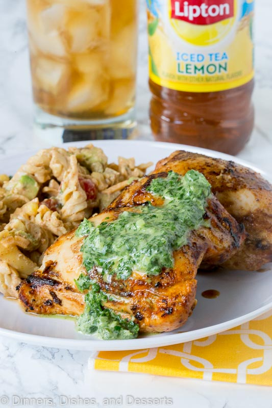 A plate of food with A plate of grilled chicken with herb sauce on top