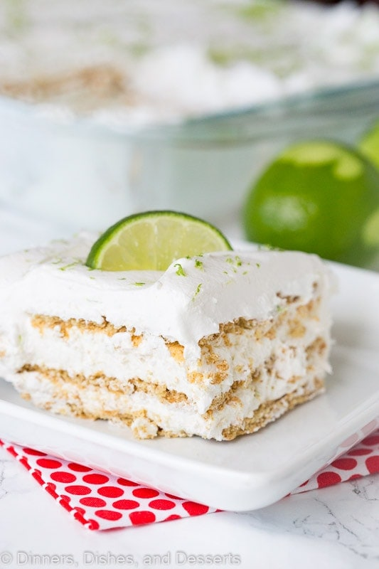 A piece of key lime ice box cake sitting on a plate with limes in the background