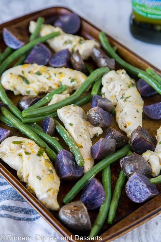chicken, green beans and purple potatoes on a baking tra