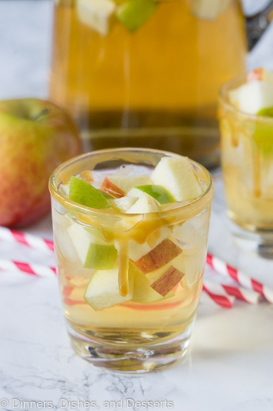 A close up of a glass cup on a table, with Sangria and Apple cider