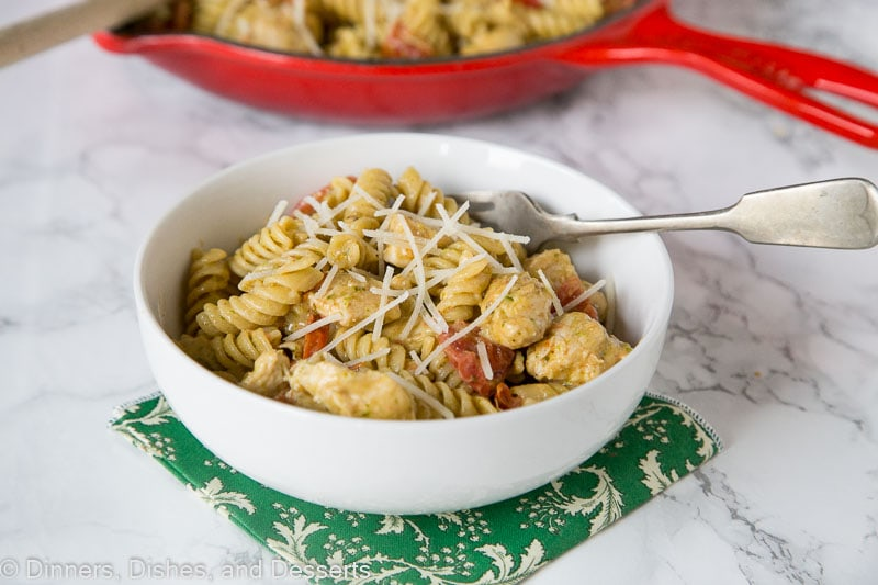 A bowl of chicken pesto pasta with a fork