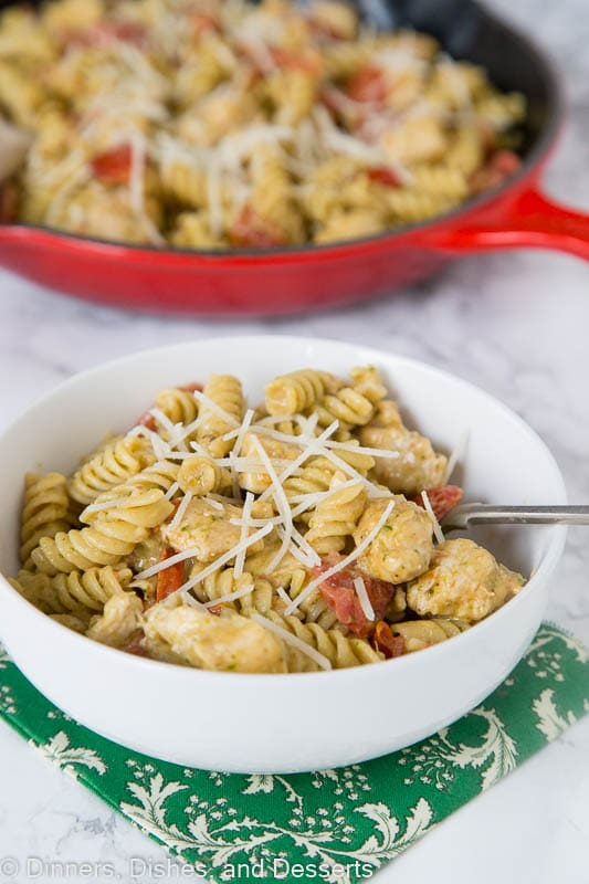 A bowl of food on a plate, with Pesto and chicken pasta