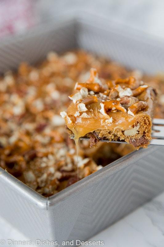 A close up of butter pecan pretzel bar next to the pan