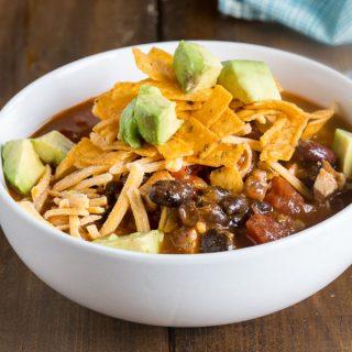 A bowl of food on a plate, with Enchilada and Soup