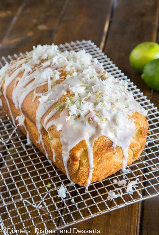 loaf of coconut lime quick bread on a cooling rack topped with lime glaze