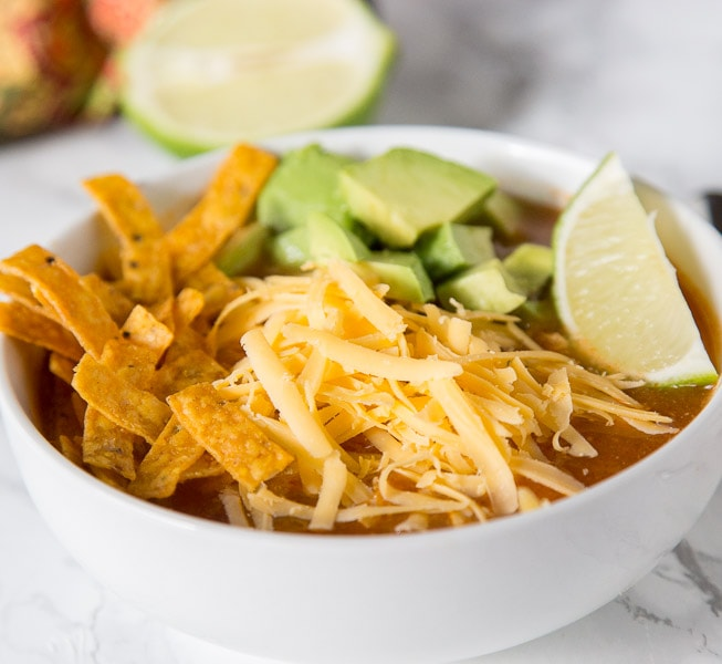 A close up tortilla soup topped with cheese